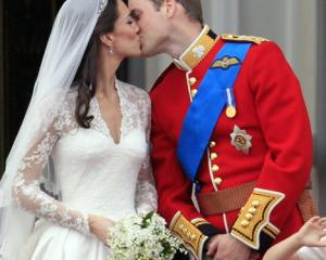 Britain's Prince William kisses his wife Kate, Duchess of Cambridge on the balcony of Buckingham...