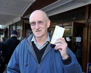 Bruce Marshall, of Dunedin, flashes his reduced price Elton John concert tickets outside the...