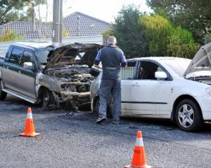 A Dunedin police photographer records the damage to two vehicles whose interiors were burned out...