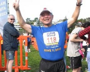 Ching-te Huang, of Taiwan, celebrates running his 106th marathon in as many weeks at the finish...