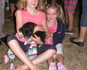 Chloe (8) and Abby (3) Wilson with an 8 week old huntaway pup.