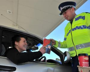 Constable Dave Bullot hands an ice scraper and free coffee to motorist Rachel Ovens at BP Connect...