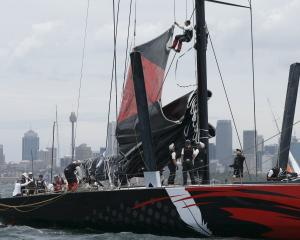 Crew members work Comanche's main mast during preparations for the start of the race on Boxing...