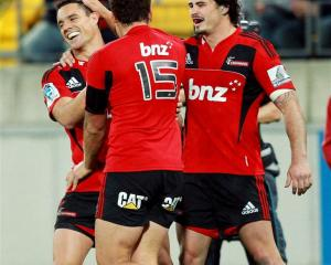 Dan Carter, Israel Dagg and Zac Guildford of the Crusaders celebrate Carter's try. (Photo by...