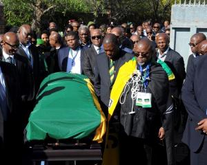 Delegates from the African National Congress transport the coffin of Nelson Mandela at his home...
