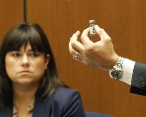 Deputy District Attorney David Walgren holds a bottle found by Los Angeles County coroner...