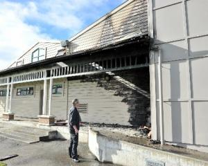 Detective Sergeant Brett Roberts examines the fire-damaged King's High School gymnasium, on...