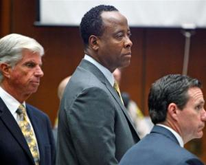 Dr Conrad Murray stands with his attorneys J. Micahel Flanagan and Edward Chernoff during his...