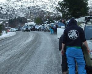 Drivers bound for Coronet Peak fit, or attempt to fit, snow chains on over 20 vehicles including...