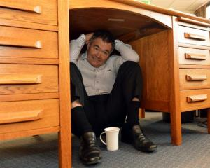 Dunedin Mayor Dave Cull shelters under his desk. Photo by Stephen Jaquiery.