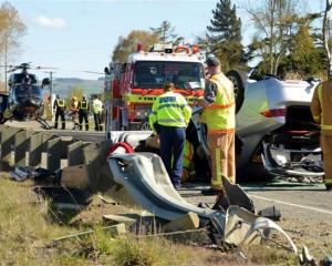 Emergency services inspect a car that overturned on State Highway 1, near Waikouaiti, yesterday....