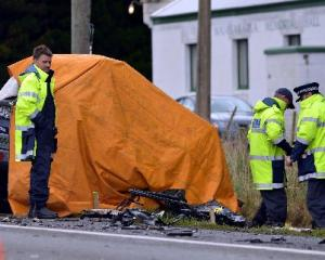 Emergency services personnel and police attend the scene of a fatal collision between a truck and...