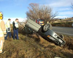 Emergency staff inspect the wreckage of a car which hit black ice and rolled on State Highway 85...