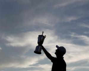 English golfer Justin Rose raises the trophy after winning the 2013 US Open at the Merion Golf...