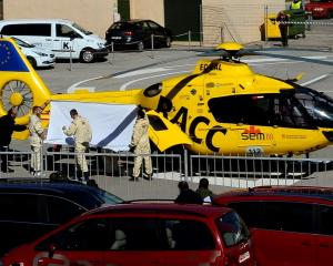 Fernando Alonso is carried to a helicopter after crashing his car during a test session at...