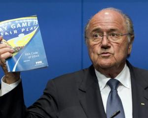 FIFA President Sepp Blatter holds the FIFA Code of Ethics while talking to the media during a...
