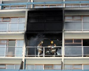 Firefighters with breathing apparatus check the room where a fire broke out on the third floor of...
