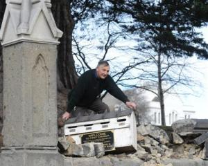 First Church caretaker Malcolm West moves the letterbox after a section of wall around the church...