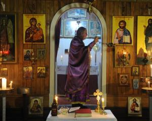 Fr Carl Somers-Edgar swings an incense burner inside St Michael's Greek Orthodox Church of...