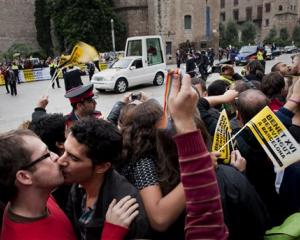 Gay activists kiss during a protest as Pope Benedit XVI passes by on his popemobile on his way to...