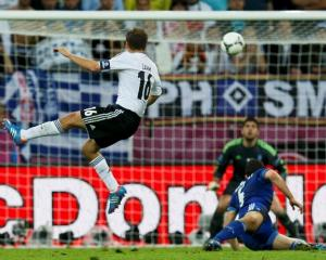 Germany's Philipp Lahm (L) scores a goal against Greece's Michalis Sifakis past Kyriakos...