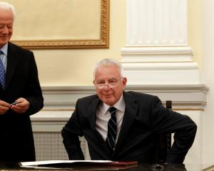 Greece's caretaker Prime Minister Panagiotis Pikrammenos (R) smiles during a swearing-in ceremony...