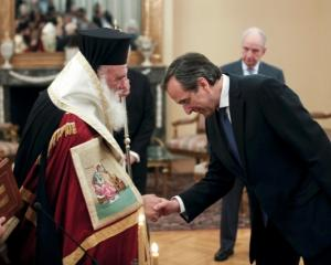 Greek Prime Minister Antonis Samaras (R) bows in front of Greece's Orthodox Archbishop Ieronymos...