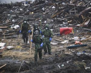Ground Self-Defence Force members search in the rain for victims' belongings in a devastated area...