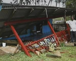 In this image taken from video, a man stands next to a destroyed houses in Suva, Fiji, after...