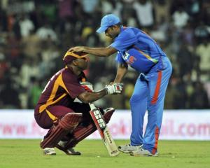 India's Irfan Pathan (R) speaks with West Indies' Kieron Pollard after Pollard was out for 119 in...