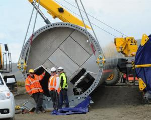 Installation crew wait out the wind beside the base section of the first wind turbine column due...