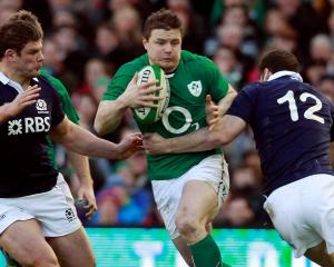 Ireland's Brian O'Driscoll (C) tries to break through the Scotland defence. REUTERS/Cathal...
