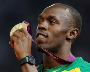 Jamaica's Usain Bolt displays his gold medal during the presentation ceremony for the men's 200m...