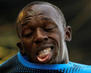Jamaica's Usain Bolt puts on his T-shirt after winning the 100m at the IAAF World Challenge...