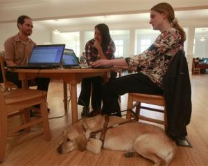 Jessie Lorenz (right) who is blind, sits with her dog Nacho as she works with engineer Mike...
