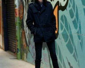 John Cooper Clarke poses in an alley across the road from the Robbie Burns statue in Dunedin...