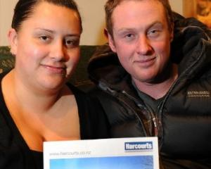 Joselle Tahana and Tim Greene with a photo of their new home in Brockville. Photo by Craig Baxter.