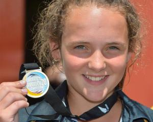 Legspinner Amelia Kerr  (14) displays her winner's medal after taking three wickets in her team's...