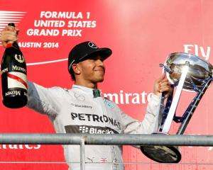 Lewis Hamilton holds up his trophy and a bottle of champagne after winning the US Grand Prix in...