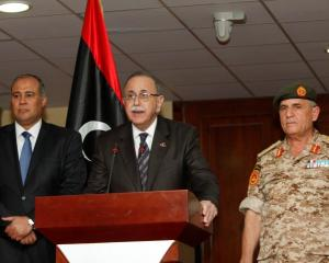 Libya's Prime Minister Abdurrahim El-Keib (C) speaks at a news conference announcing that the...