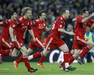 Liverpool's players react after winning on penalties against Cardiff City during their English...