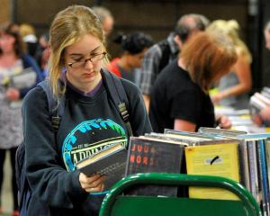 Mackenzie Reid browses  books in the Dunedin Public Libraries' book sale yesterday. Photo by...