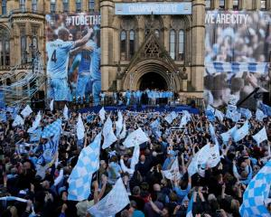 Manchester City players celebrate with their English Premier League trophy outside Manchester...