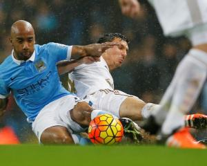 Manchester City's Fabian Delph (L) contests the ball with Swansea City's Jack Cork. Photo Reuters