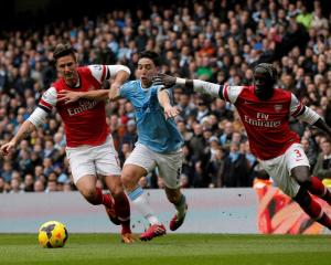 Manchester City's Samir Nasri (C) is challenged by Arsenal's Olivier Giroud (L) and Bacary Sagna....