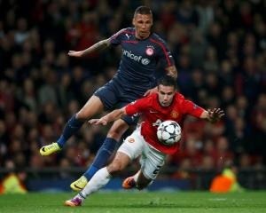 Manchester United's Robin van Persie (front) is fouled for penalty by Olympiakos' Jose Holebas....