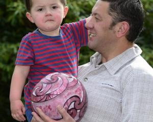 Manuaitu Haggie (2) at home with his father, Reihana, and the carved bowling ball up for auction....