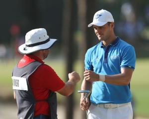 Martin Kaymer (right) celebrates with caddie Craig Connolly after making a putt on the 17th hole....