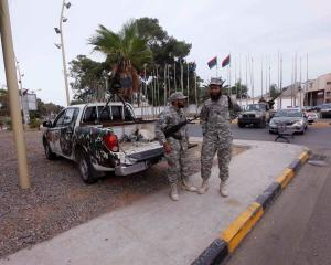 Members of the Libyan security forces stand guard close to the headquarters of the General...