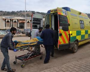 Men transport a casualty after car bomb attacks occurred at the Bab al-Hawa border crossing...